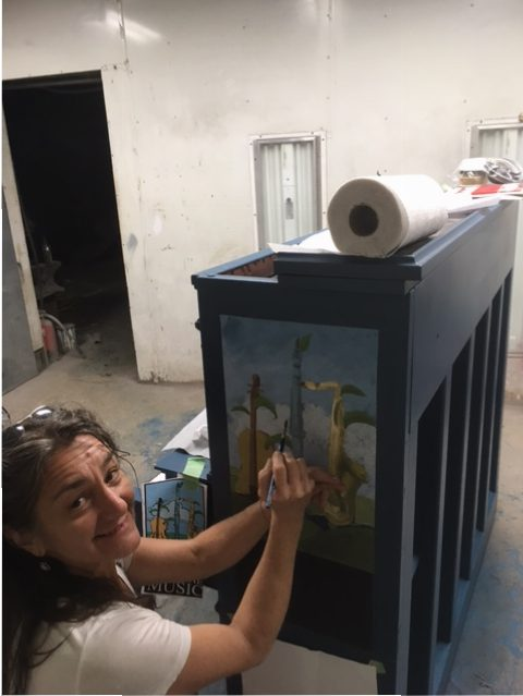Caroline Connors painting a piano